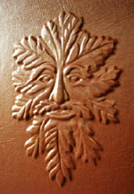 custom rust leather book of shadows with carved green man and elemental symbols front detail 2