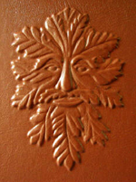 custom rust leather book of shadows with carved green man and elemental symbols front detail 1