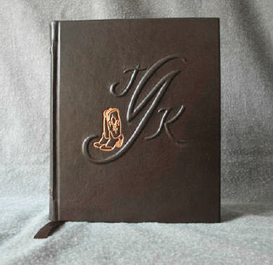 dark brown leather anniversary journal with monogram and cowboy boots